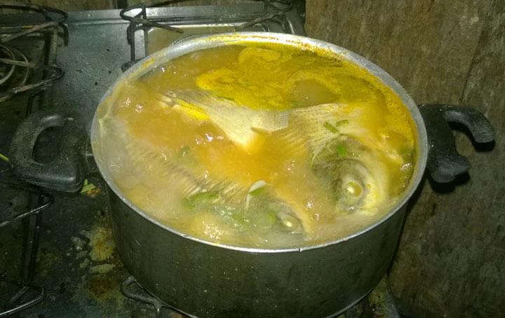 Suppe aus selbstfefangenen Fischen auf dem Gasherd in der einfachen Küche.