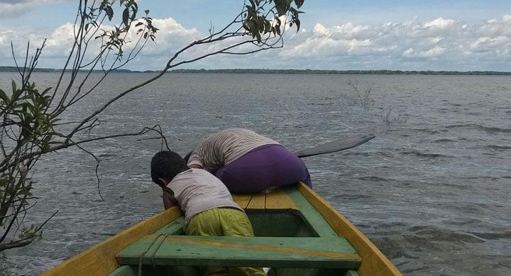 Eliana und ihr Cousim Lucas holen Netze aus dem See. Auf der linken Seite ragen überflutete Sträucher ins Bild.